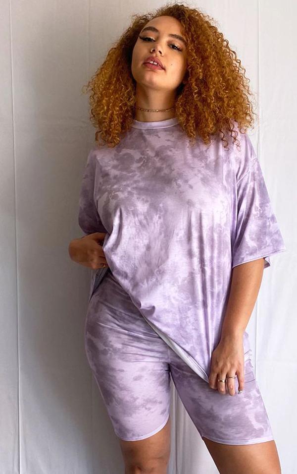 A plus-size model wearing purple tie-dye bike shorts.