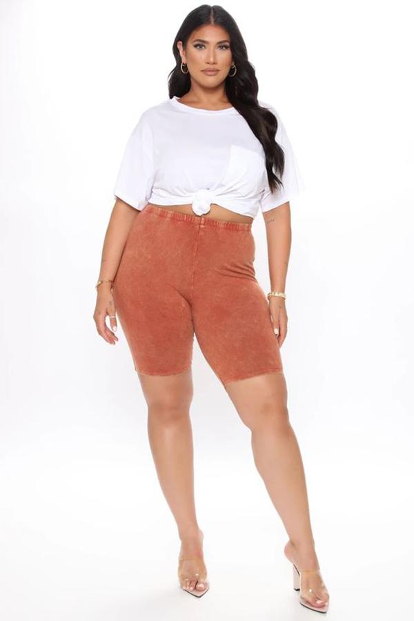 A plus-size model wearing rust bike shorts.