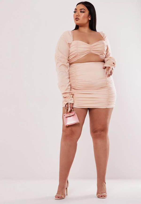A plus-size model wearing a light pink matching set.