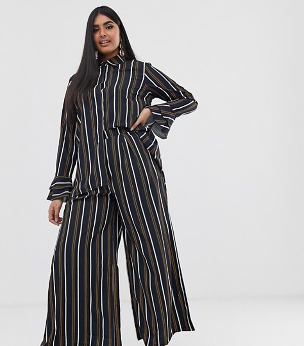 A plus-size model wearing a black striped matching set.