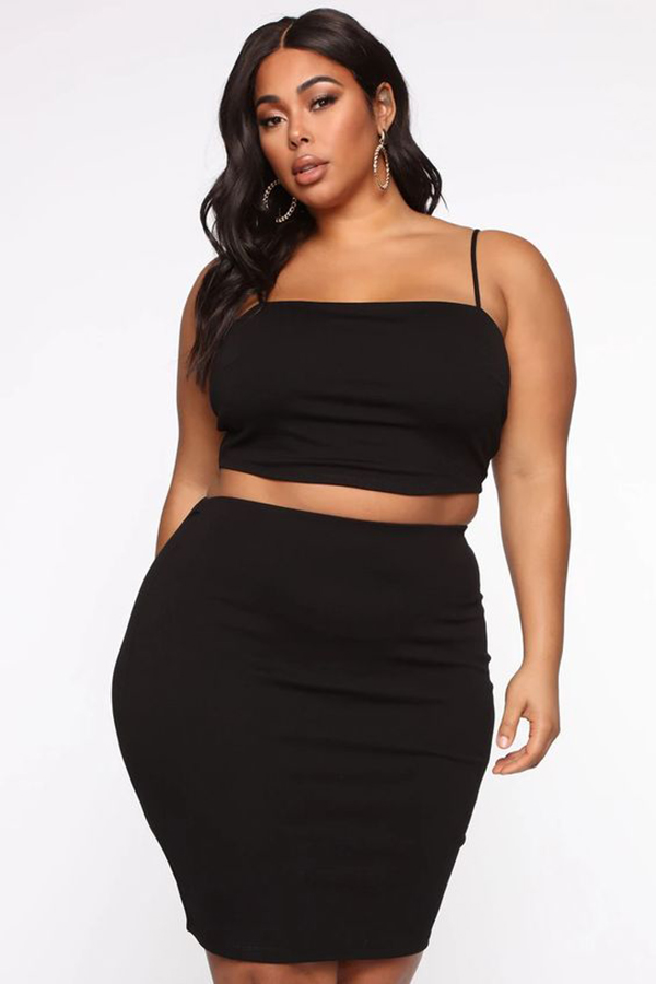 A plus-size model wearing a black matching set.