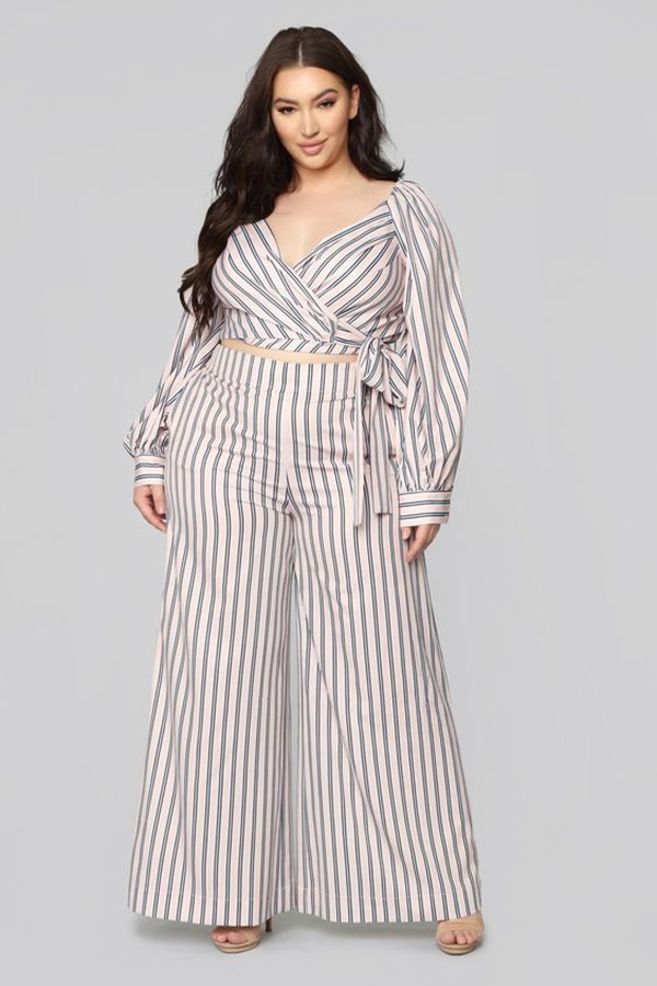 A plus-size model wearing a pinstripe matching set.