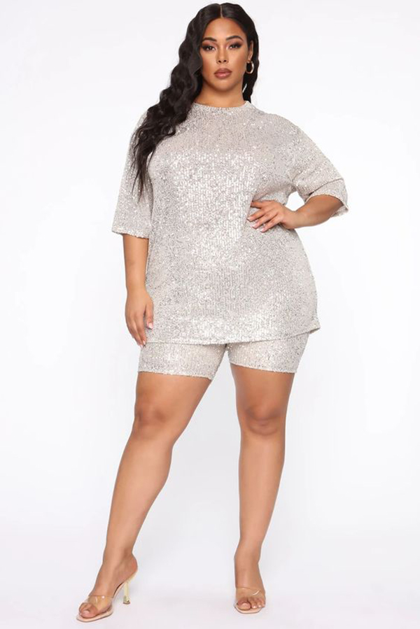 A plus-size model wearing a silver sequin matching set.