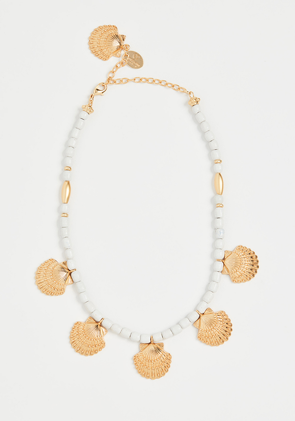 A white beaded necklace with metal scallop shells on it.