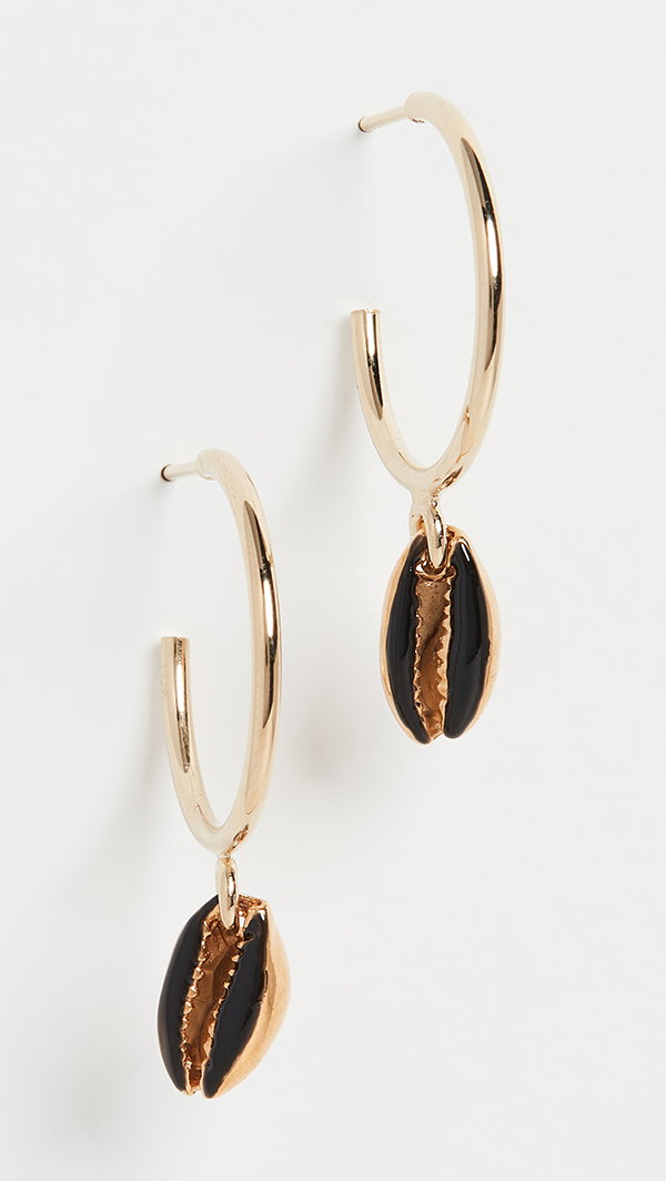 A pair of gold hoop earrings with painted metal cowrie shells hanging from them.