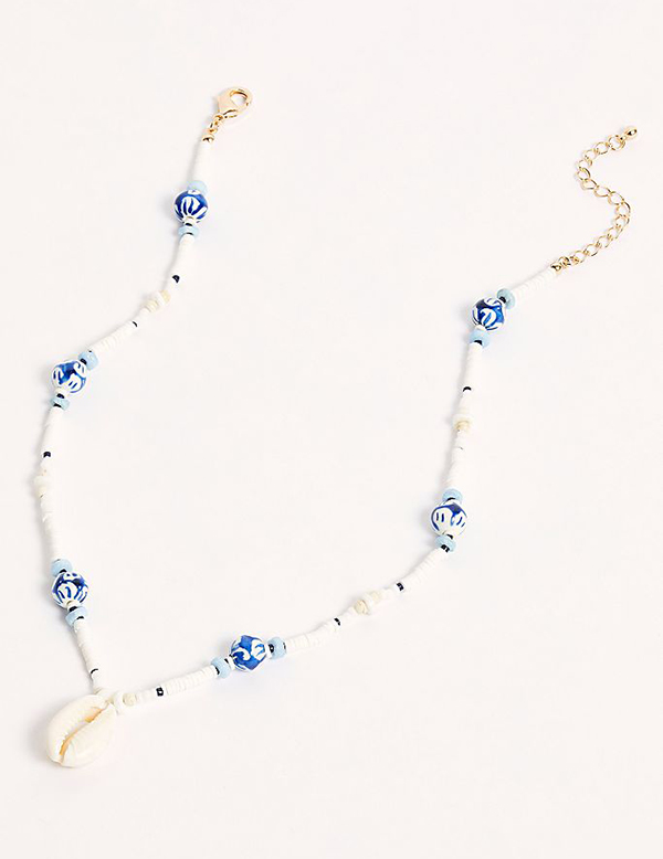 A blue beaded necklace with a cowrie shell at the end of it.
