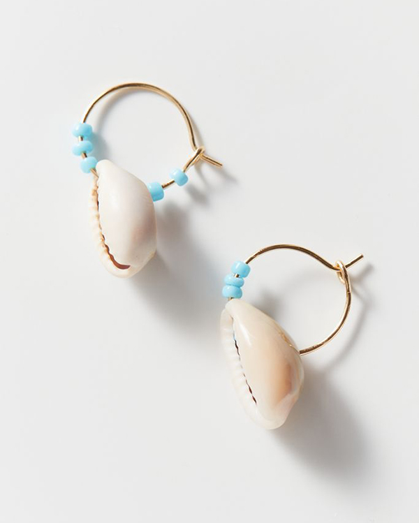 A pair of cowrie shell hoop earrings.
