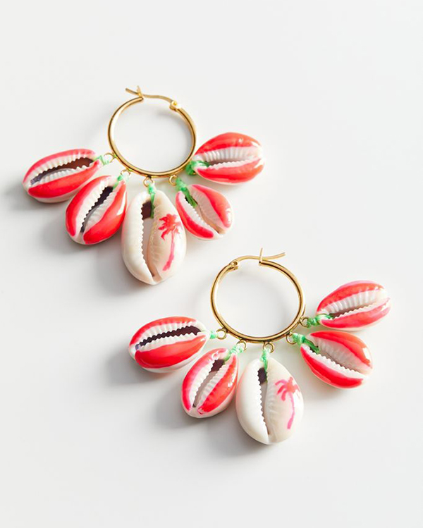 A pair of hoop earrings with painted red cowrie shells on them.