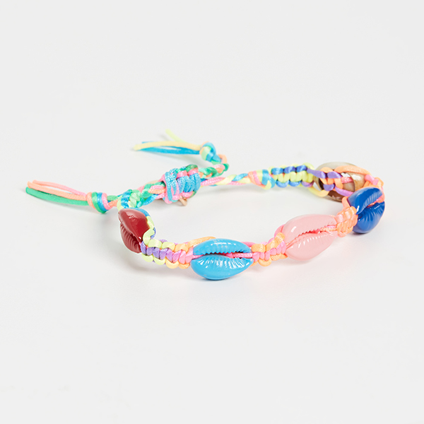 A rainbow woven bracelet with rainbow woven cowrie shells on it.