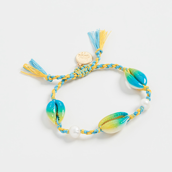A blue and yellow woven bracelet with painted cowrie shells on it.
