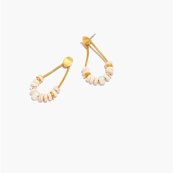 A pair of drop earrings lined with rounded puka shell beads.
