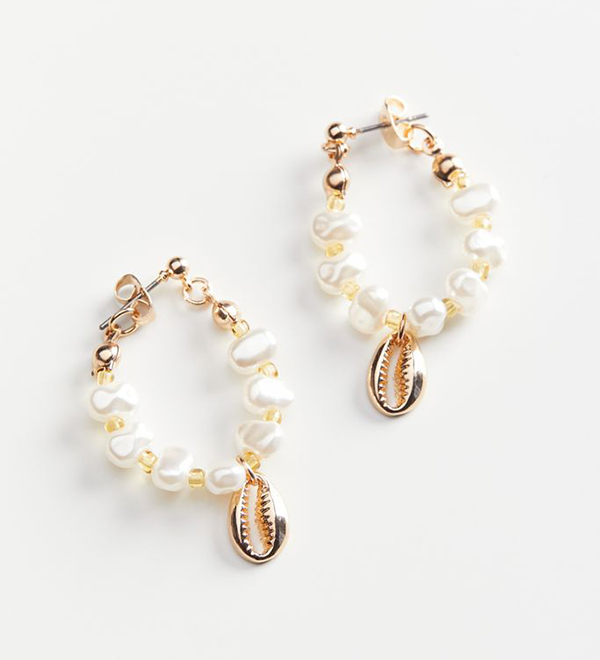 A pair of pearl drop earrings with gold metal cowrie shells dangling from them.