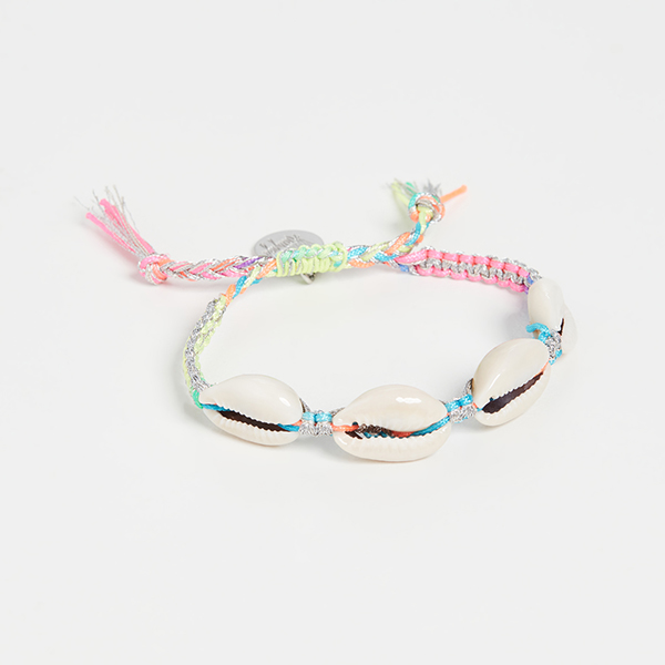 A pastel woven bracelet with cowrie shells on it.