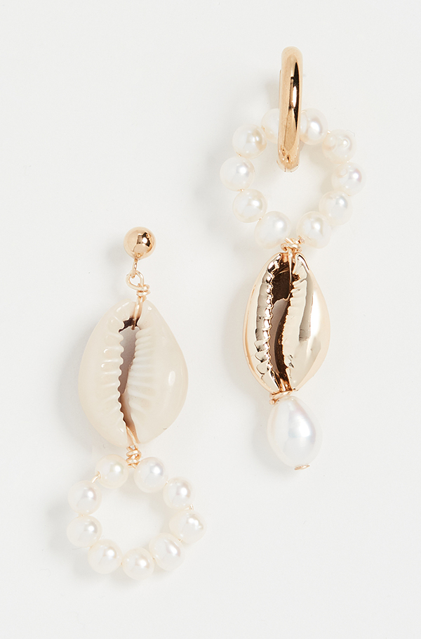 A pair of asymmetrical drop earrings crafted from pearls and cowrie shells.