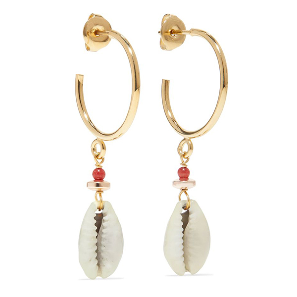 A pair of gold hoop earrings with cowrie shells hanging from them.