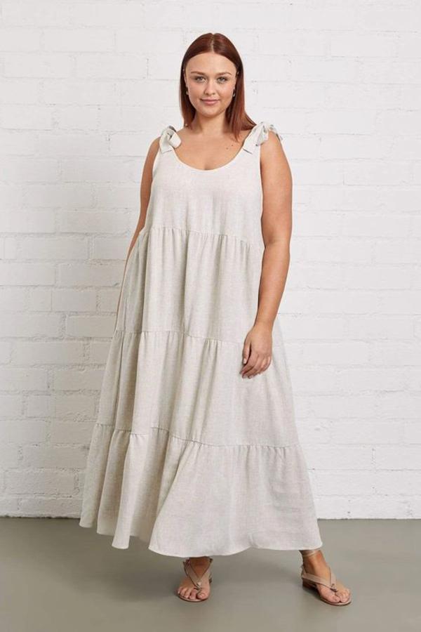 A plus-size model wearing a white tie-strap dress.