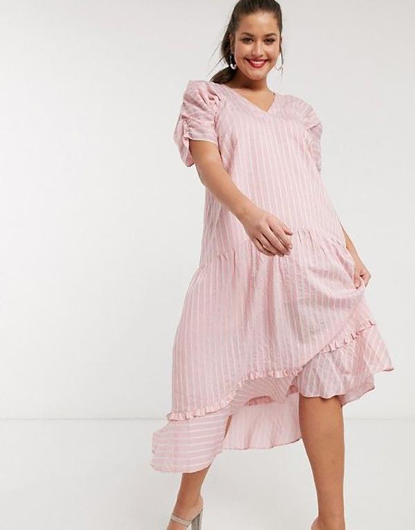 A plus-size model wearing a pink pinstripe dress.
