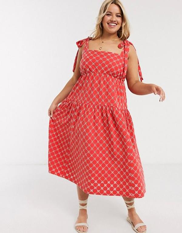A plus-size model wearing a red tie-strap dress.
