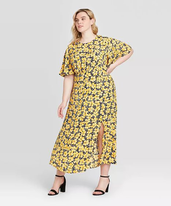A plus-size model wearing a yellow floral dress.