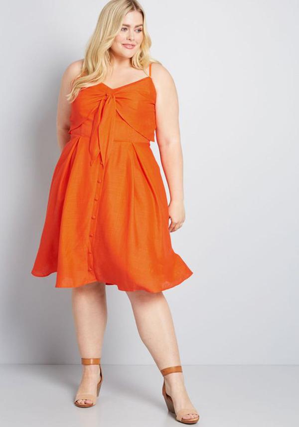 A plus-size model wearing an orange dress.