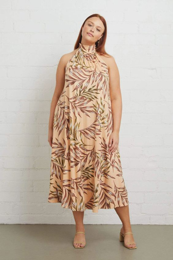 A plus-size model wearing a peach tropical print dress.