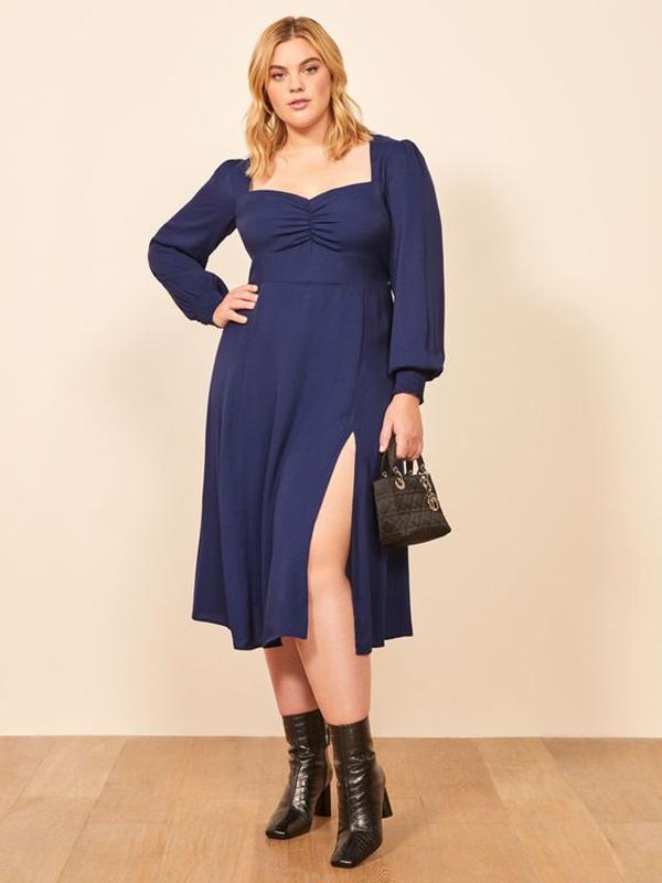 A plus-size model wearing a navy dress.