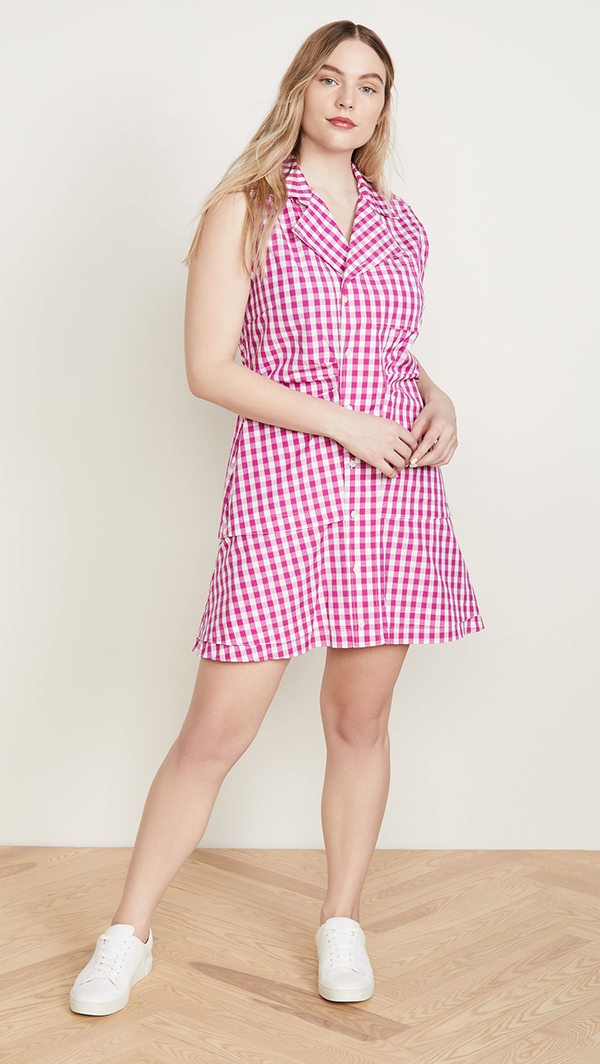 A plus-size model wearing a hot pink gingham dress.