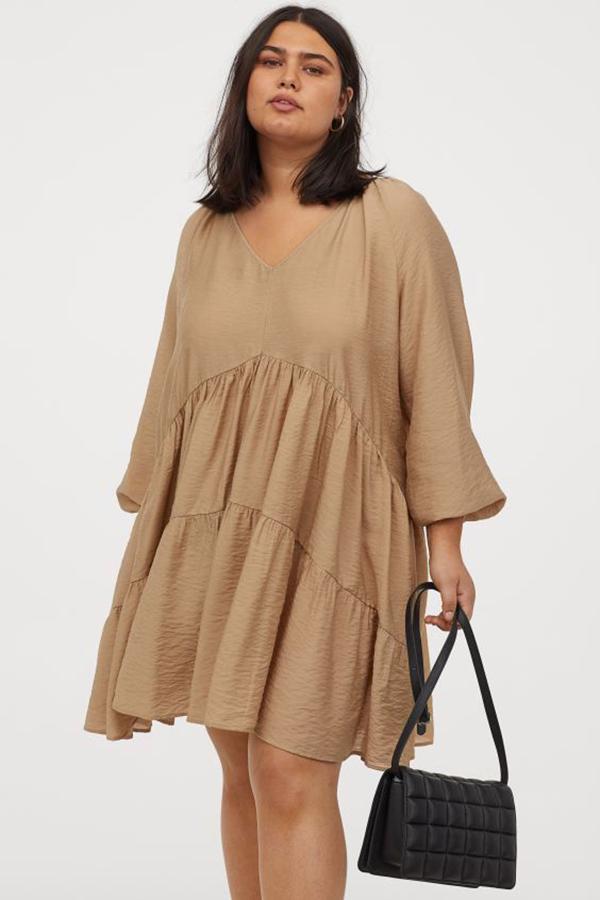 A plus-size model wearing a tan shift dress.