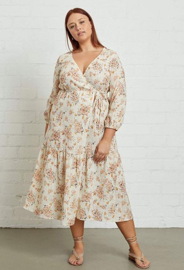 A plus-size model wearing a floral wrap dress.