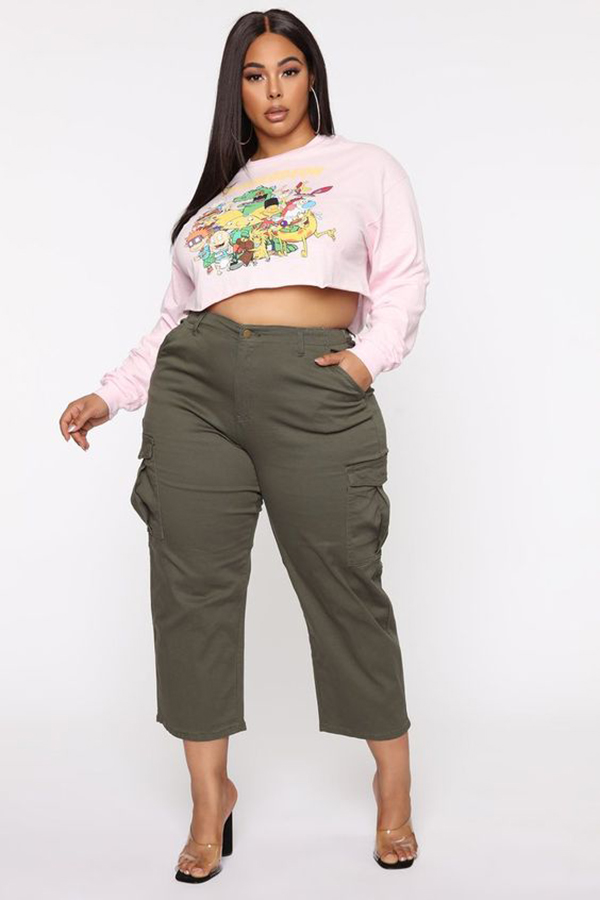 A plus-size model wearing cropped olive cargo pants.