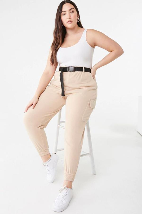 A plus-size model wearing light beige cargo pants.