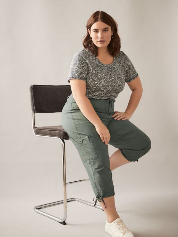 A plus-size model wearing olive cargo pants.