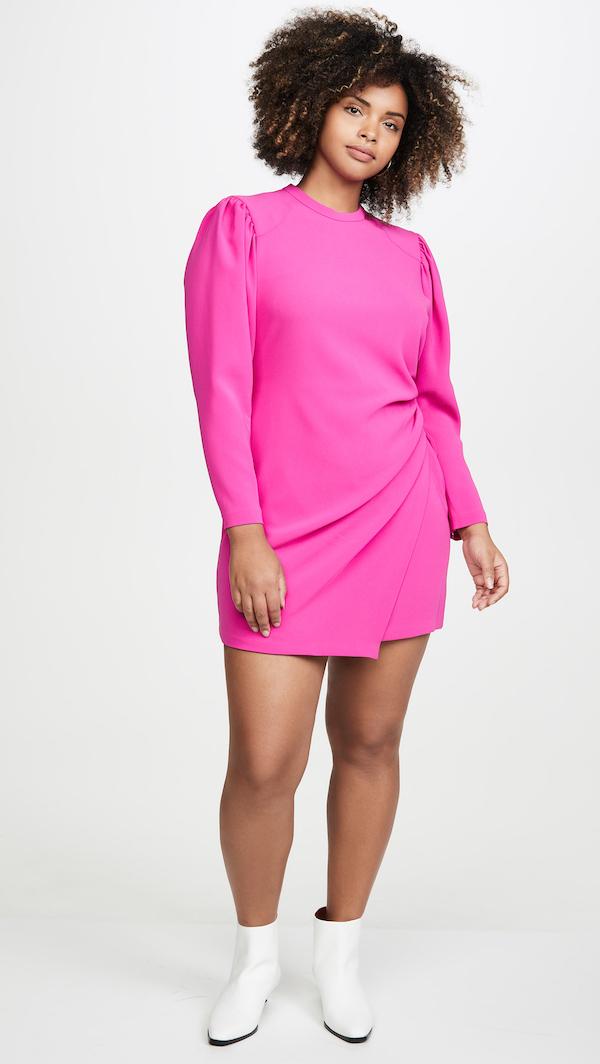 A plus-size model wearing a neon pink mini dress.
