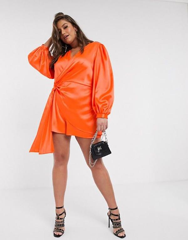 A plus-size model wearing a neon orange romper.