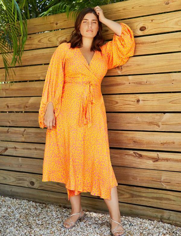 A plus-size model wearing a neon orange, animal print dress.