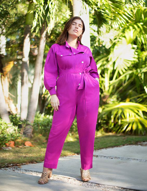 A plus-size model wearing a neon fuchsia utility jumpsuit.