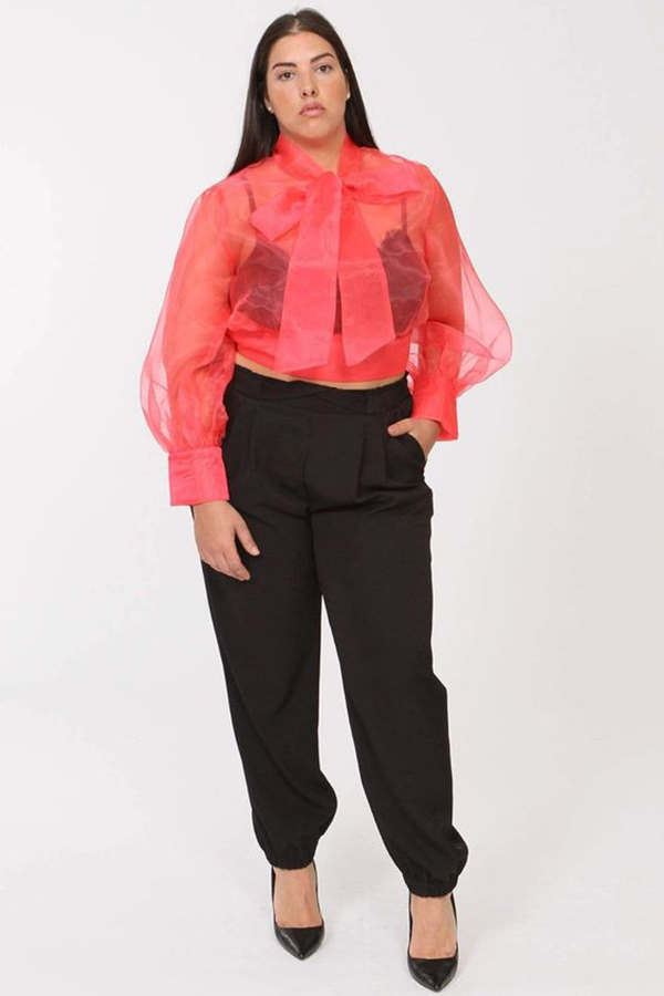 A plus-size model wearing a neon coral transparent blouse.