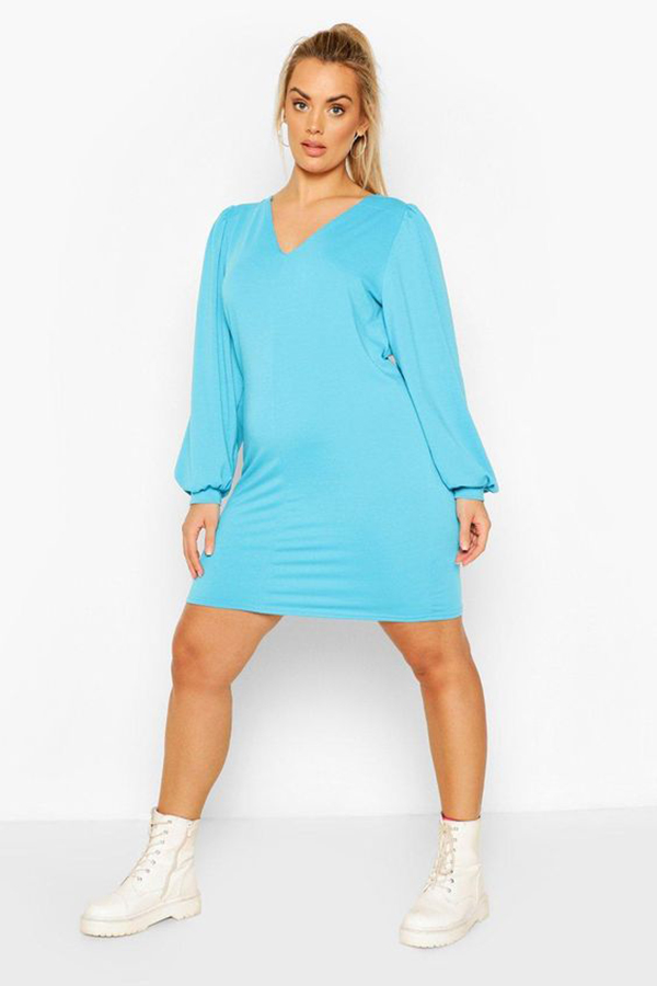 A plus-size model wearing a neon blue dress.