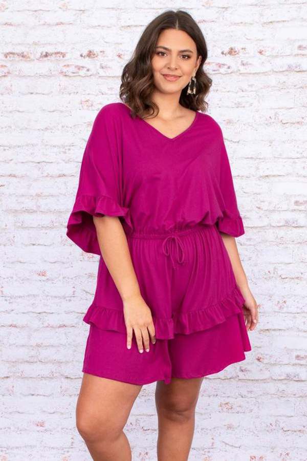 A plus-size model wearing a maroon romper.
