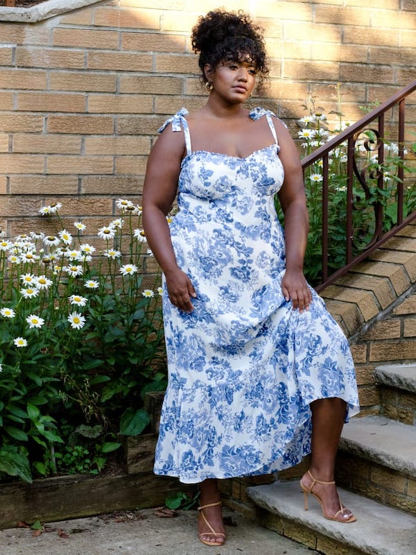 A woman wearing a blue and white maxi dress from Reformation.