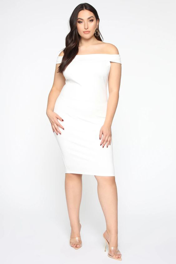 A plus-size model wearing a figure-hugging white midi dress.
