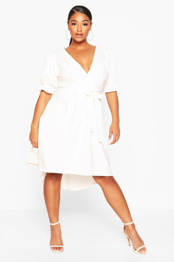 A plus-size model wearing a white wrap dress.