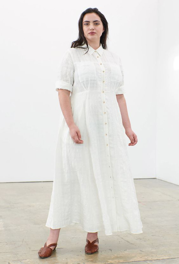 A plus-size model wearing a tailored white maxi dress.