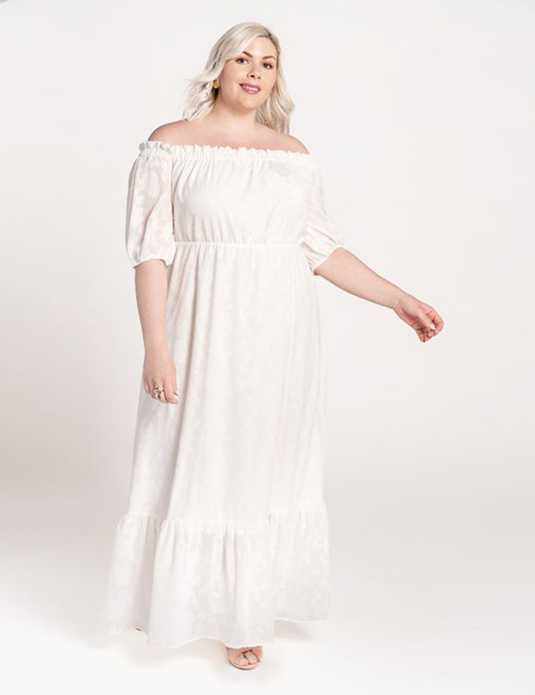 A plus-size model wearing an off-the-shoulder white maxi dress.