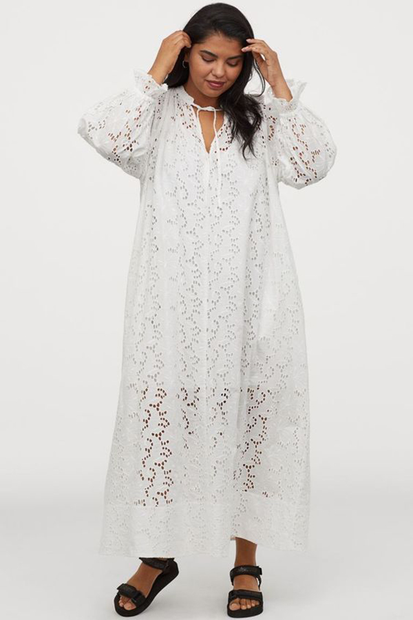 A plus-size model wearing a white lace maxi dress.