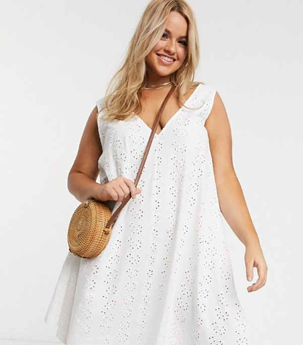 A plus-size model wearing a white lace mini dress.