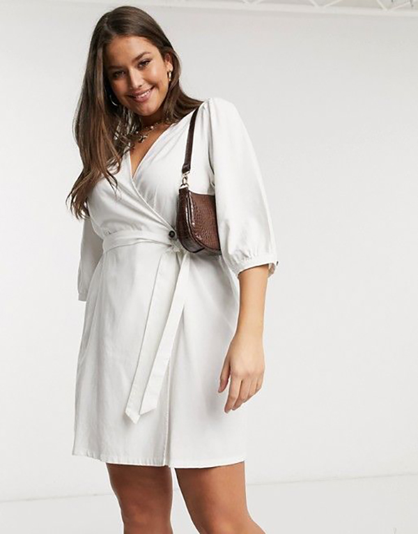 A plus-size model wearing a white wrap mini dress.