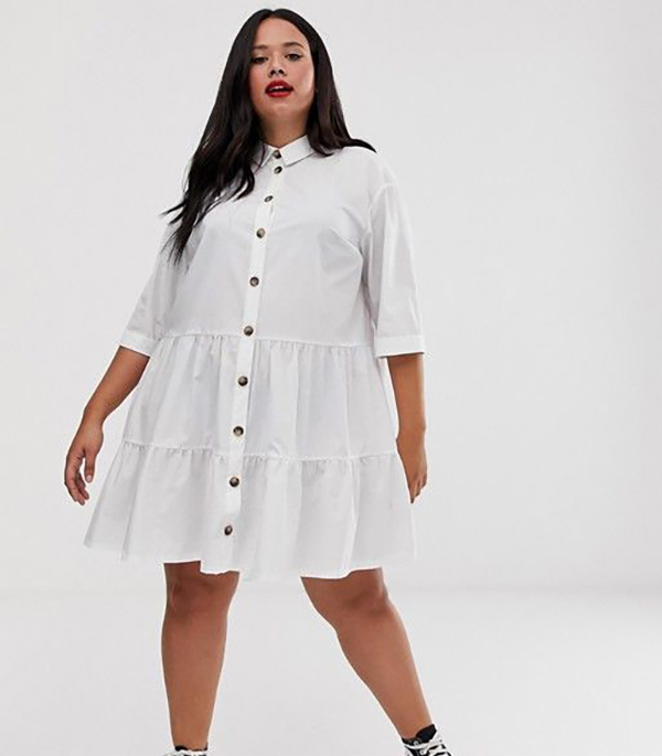 A plus-size model wearing a white button-up shirtdress.