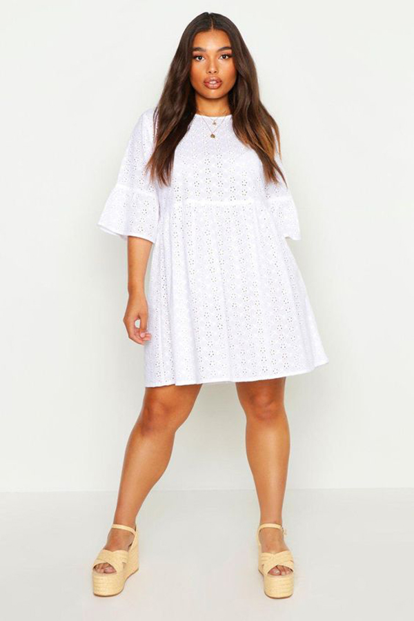 A plus-size model wearing a white sundress.