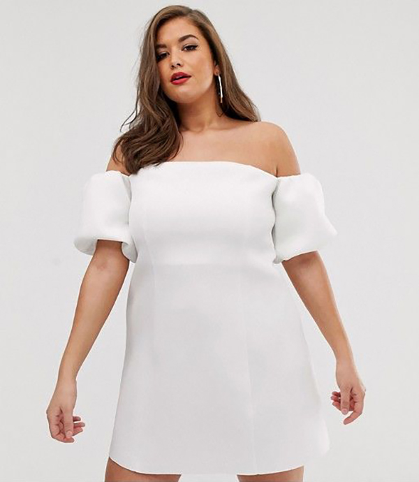 A plus-size model wearing an off-the-shoulder white dress.